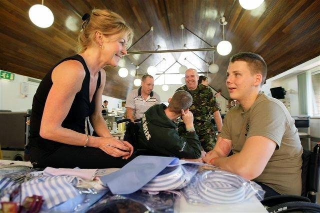 Emma Willis MBE, talking to one of the young service personnel she has made a bespoke shirt for.