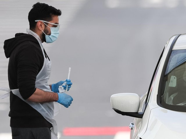 A tester administers a coronavirus test at a testing site near Manchester Airport, as the UK continues in lockdown to help curb the spread of the coronavirus. Photo: PA