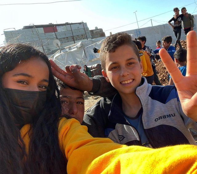 Halima Asker, from Sheffield, with some of the refugees she met while distributing care packages in Lebanon