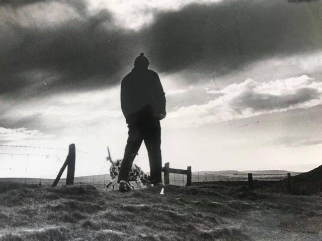 A man walking his dog on the Ringlow to Hathersage Road with Higger Tor to the right in the background - December 1977