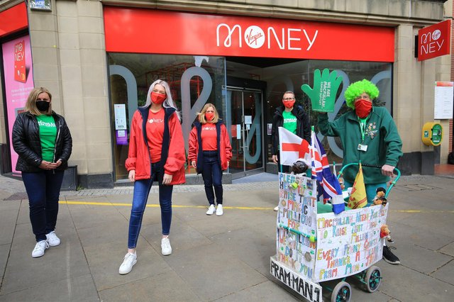 John Burkhill took his first walk around Sheffield today with the help of staff from Virgin Money on Fargate. Picture: Chris Etchells