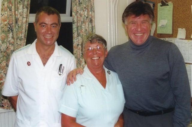 Footballer Emlyn Hughes with St Luke's Hospice staff