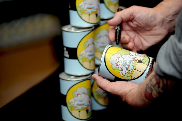 Pete McKee with some of the specially-designed soup tins that the first 500 members of the public received in return for donations to a pop-up food bank on Division Street in Sheffield in June 2018