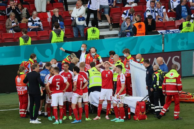 Christian Eriksen (hidden) receives medical treatment during the UEFA Euro 2020 Championship Group B match between Denmark and Finland on June 12, 2021 in Copenhagen, Denmark. (Photo by Wolfgang Rattay - Pool/Getty Images)