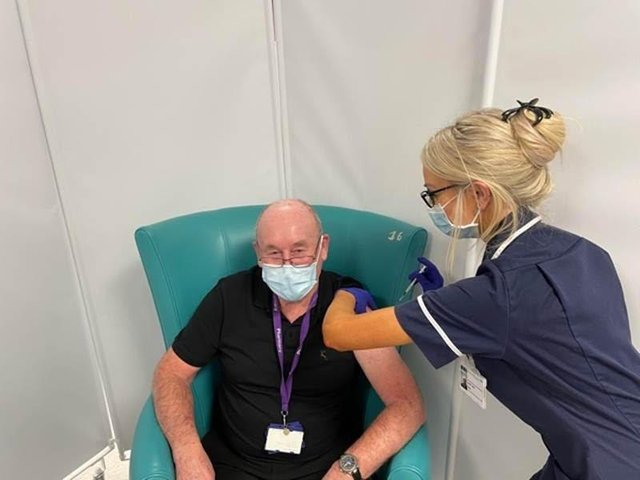 Michael Burnell who works supporting the Sheffield Hospitals Pharmacy team aged 81 having his vaccination from Sister Amber Mills.