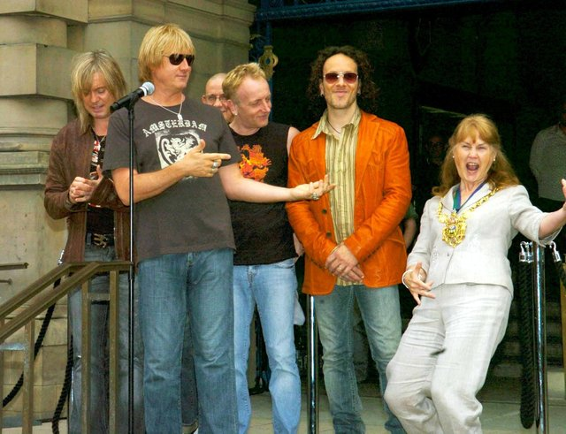 Rock group Def Leppard watch as Sheffield Lord Mayor Jackie Drayton performs 'air guitar'  before they unveiled a plaque on Sheffield's Walk of Fame in June 2006