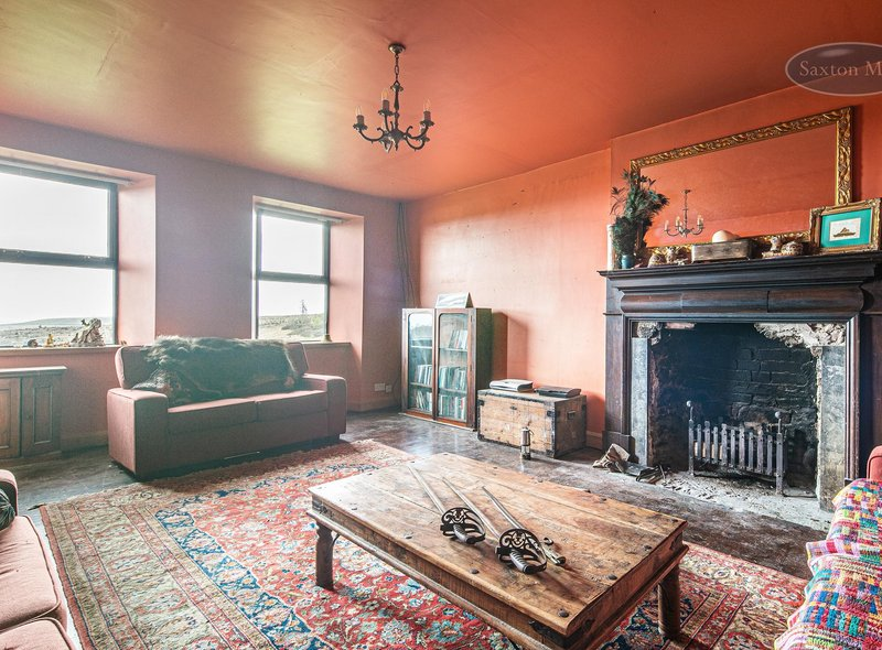 The drawing room features a large fireplace, a bay window, a door to the front lawn and original panelling.