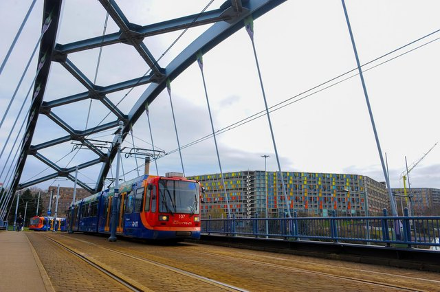 A Supertram crosses the Commercial Street Bridge with the iconic Park Hill flats in the background on its way in to the city centre