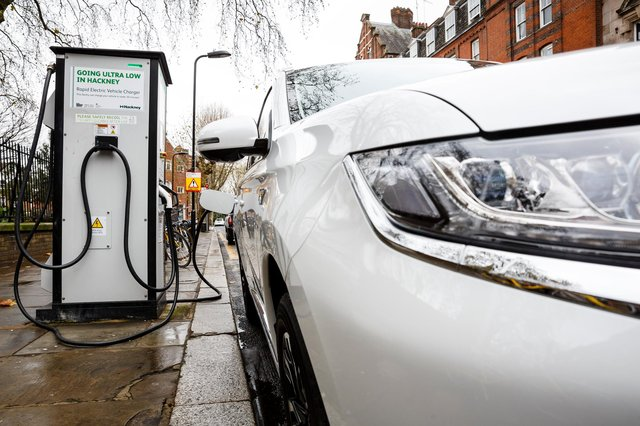 Go Ultra Low Mitsubishi Outlander PHEV on charge on a London street. Ultra-low emission vehicles such as this can cost as little as 2p per mile to run and some electric cars and vans have a range of up to 700 miles.