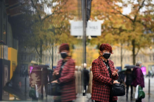 A woman is reflected in a window as she leaves a shop in central Sheffield (Photo by OLI SCARFF/AFP via Getty Images)