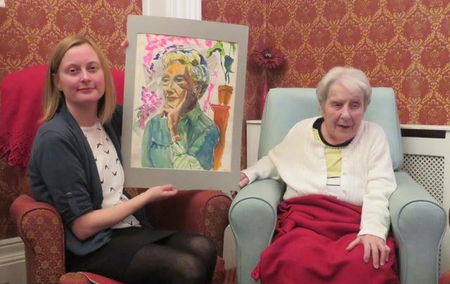 Sheffield artist Joyce Spurr presenting her painting of Enid Hattersley to Museums Sheffield curator Clara Morgan
