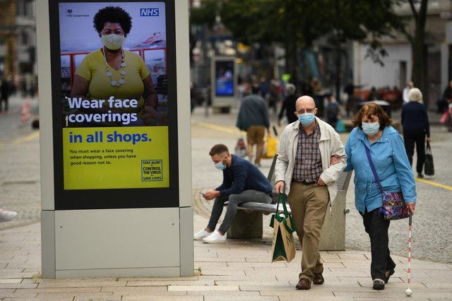 Shoppers wearing face masks walk past a sign calling for the wearing of face coverings in shops, in the city centre of Sheffield (Photo by Oli SCARFF / AFP) (Photo by OLI SCARFF/AFP via Getty Images)