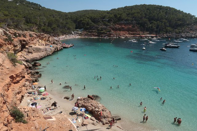 Bathers relax at Cala Saladeta beach on the island of Ibiza  (Photo by Sean Gallup/Getty Images)