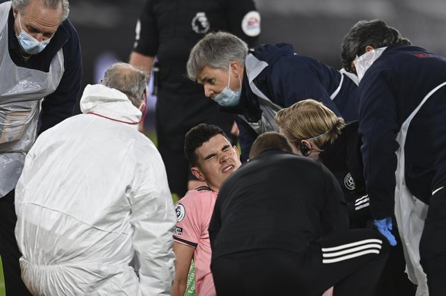 Sheffield United's John Egan is attended to by medics before being stretchered off at West Ham (Glyn Kirk/Pool via AP)
