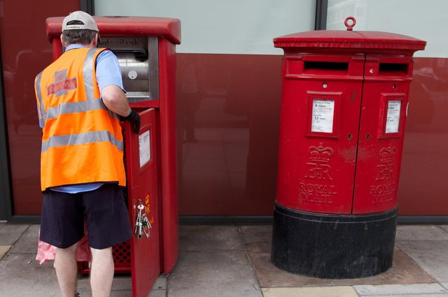 A postman empties a Royal Mail post box        (Photo credit should read ANDREW COWIE/AFP via Getty Images)