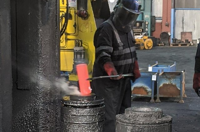 Ian Turner, forge operative, placing a hot blank into the forging machine at IFA.