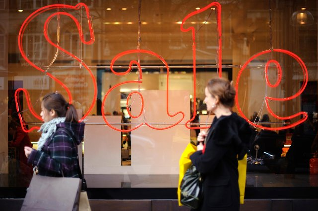 Pedestrians pass a store advertising sales discounts. Picture: Frantzesco Kangaris/Bloomberg via Getty Images.