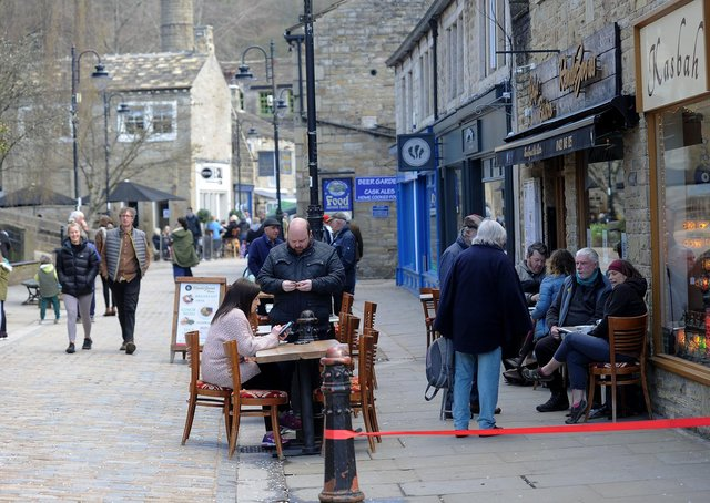 People sit outside bars and cafes at Hebden Bridge, as Covid 19 restrictions are relaxed..12th April 2021..Picture by Simon Hulme