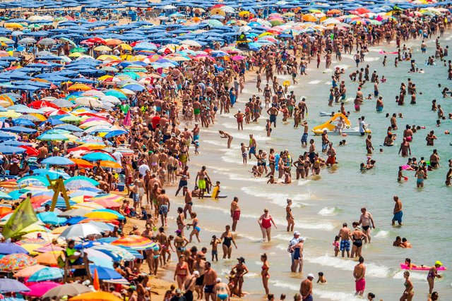 People sunbathe at Levante Beach (Photo by David Ramos/Getty Images)