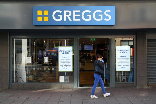 An woman wearing a face mask as a precautionary measure against covid-19, walks past a Greggs (Photo by GEOFF CADDICK / AFP) (Photo by GEOFF CADDICK/AFP via Getty Images)