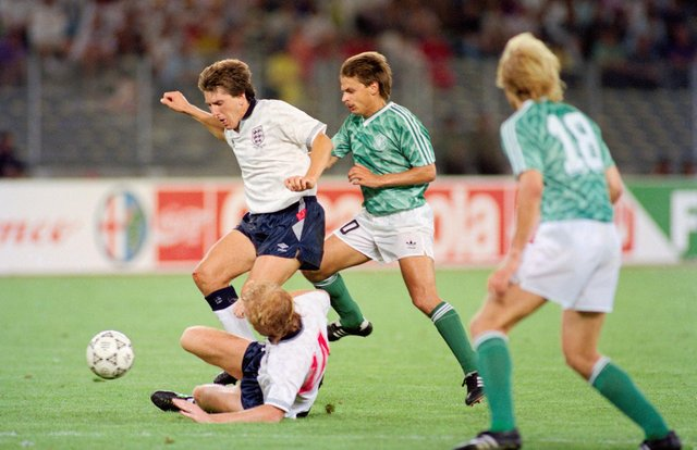 TURIN, ITALY - JULY 04:  England players Mark Wright (floor) and Peter Beardsley combine to thwart Olaf Thon of West Germany during the 1990 FIFA World Cup Semi Final at Stadio delle Alpi on July 4th, 1990 in Turin, Italy.  (Photo by Simon Bruty/Allsport/Getty Images)