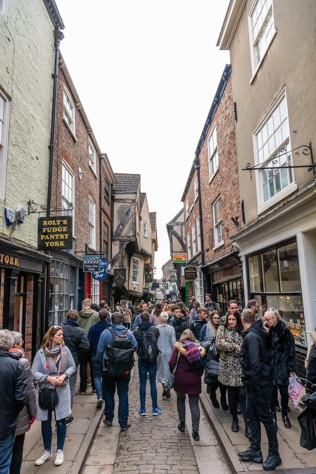Pedestrians pictured walking along The Shambles, York.