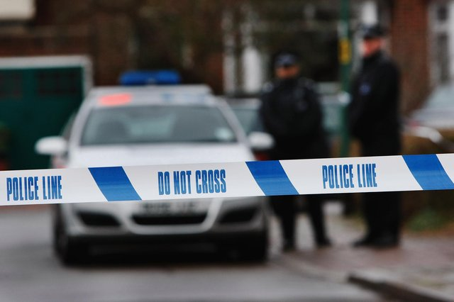 Police tape is pictured as police officers stand guard (Photo by Daniel Berehulak/Getty Images)