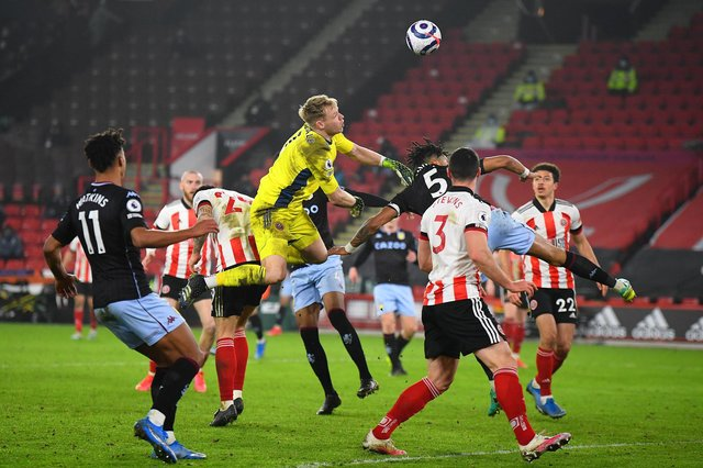 Aaron Ramsdale of Sheffield United clears the ball under pressure from Tyrone Mings of Aston Villa  during the Premier League match between Sheffield United and Aston Villa at Bramall Lane . (Photo by Clive Mason/Getty Images)