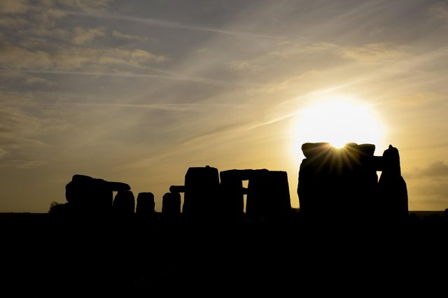AMESBURY, ENGLAND - DECEMBER 22:  The sun rises over Stonehenge,  as people take part in solstice ceremony at the ancient neolithic monument of Stonehenge near Amesbury  (Photo by Matt Cardy/Getty Images)
