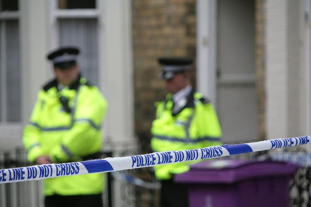 Police officers stand outside a house (Photo by Christopher Furlong/Getty Images)