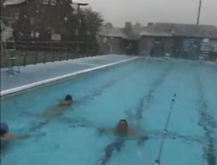 Watch hardy swimmers take the plunge outside as snow falls in Peak District