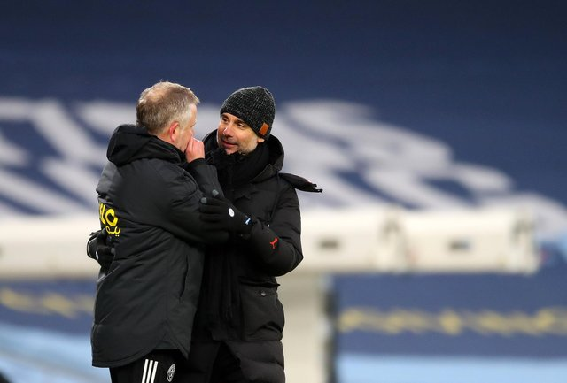 Josep Guardiola and Chris Wilder talk after the final whistle at the Etihad Stadium: Darren Staples/Sportimage