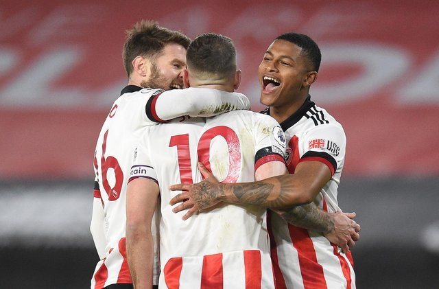 SHEFFIELD, ENGLAND - JANUARY 12: Billy Sharp of Sheffield United celebrates with Oliver Norwood (L) and Rhian Brewster (R) after scoring a penalty for his teams first goal during the Premier League match between Sheffield United and Newcastle United at Bramall Lane on January 12, 2021 in Sheffield, England. Sporting stadiums around England remain under strict restrictions due to the Coronavirus Pandemic as Government social distancing laws prohibit fans inside venues resulting in games being played behind closed doors. (Photo by Oli Scarff - Pool/Getty Images)