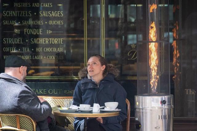 People keep warm next to a heater. PA Phot: Dominic Lipinski/PA Wire