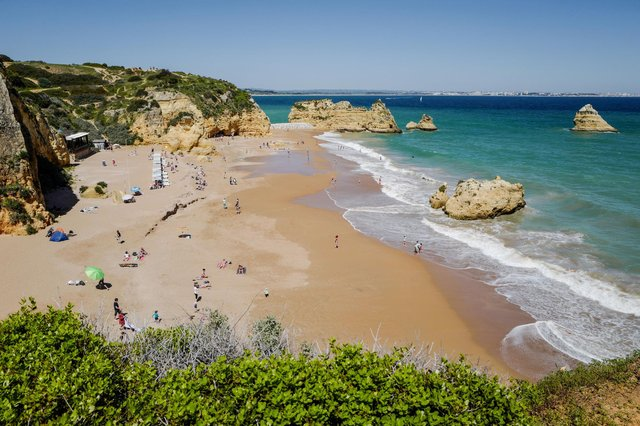 People enjoy the warm weather at the Dona Ana beach in Lagos on April 18, 2018 in the southern Portugal region of Algarve. (Photo by Ludovic MARIN / AFP)        (Photo credit should read LUDOVIC MARIN/AFP via Getty Images)