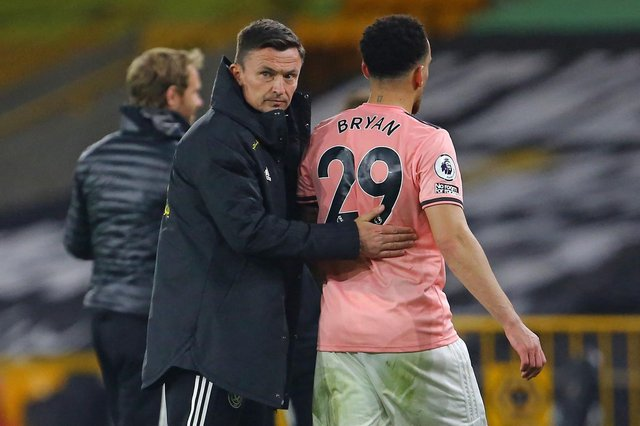 Sheffield United's Interim manager Paul Heckingbottom (L) consoles Sheffield United's English midfielder Kean Bryan as defeat means they are relegated from the Premier League, after the English Premier League football match between Wolverhampton Wanderers and Sheffield United at the Molineux stadium in Wolverhampton, central England on April 17, 2021. - Wolves won the game 1-0, Sheffield United are relegated. (Photo by GEOFF CADDICK / POOL / AFP) / RESTRICTED TO EDITORIAL USE. No use with unauthorized audio, video, data, fixture lists, club/league logos or 'live' services. Online in-match use limited to 120 images. An additional 40 images may be used in extra time. No video emulation. Social media in-match use limited to 120 images. An additional 40 images may be used in extra time. No use in betting publications, games or single club/league/player publications. /  (Photo by GEOFF CADDICK/POOL/AFP via Getty Images)