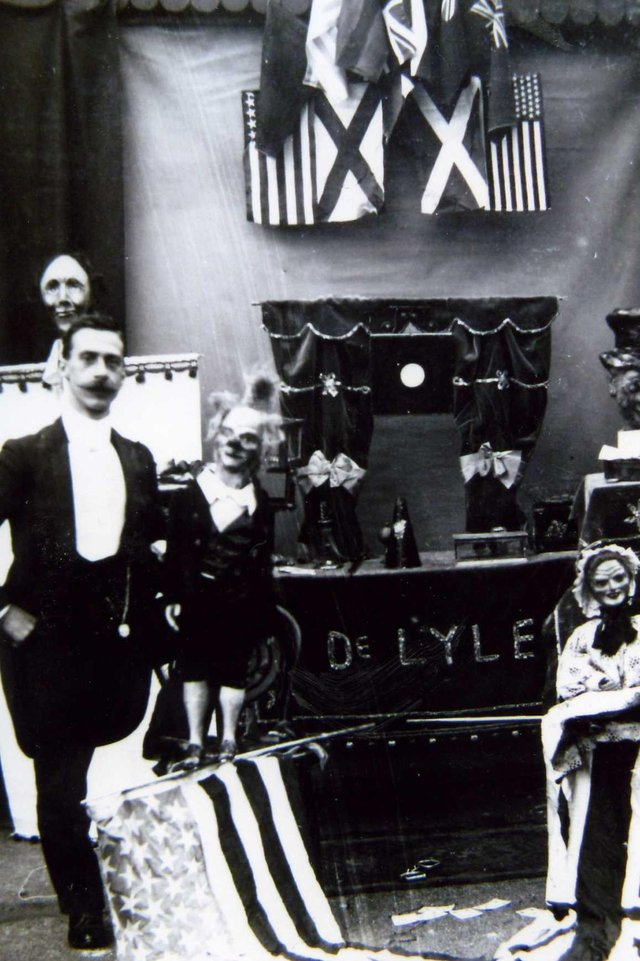 Professor De Lyle with puppets and props - he used this image on a card advertising his act
