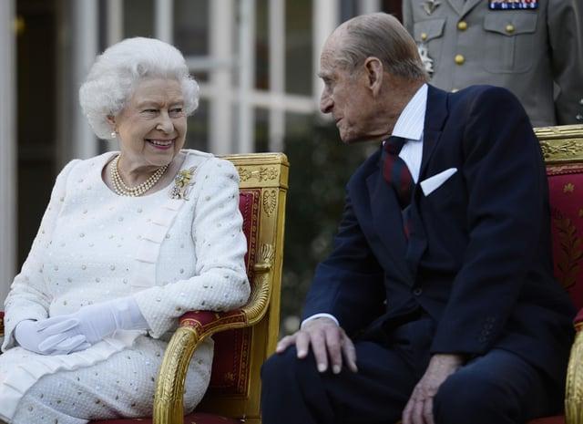 Queen Elizabeth II and the Duke of Edinburgh attending a garden party in Paris - PA