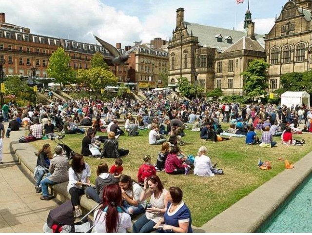 People enjoying the sun in the city centre.