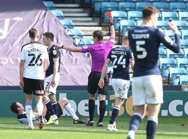 Rotherham United's Richard Wood (on the ground) is shown the red card during the Sky Bet Championship match at The Den. Jonathan Brady/PA Wire.