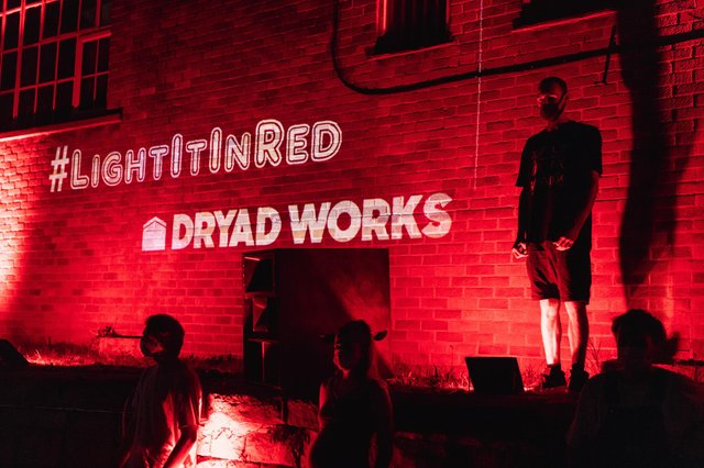 Joe (top right) and others at Dryad Works when it was lit up red in August. Photo by Rhys Belding/Blueshift Studios