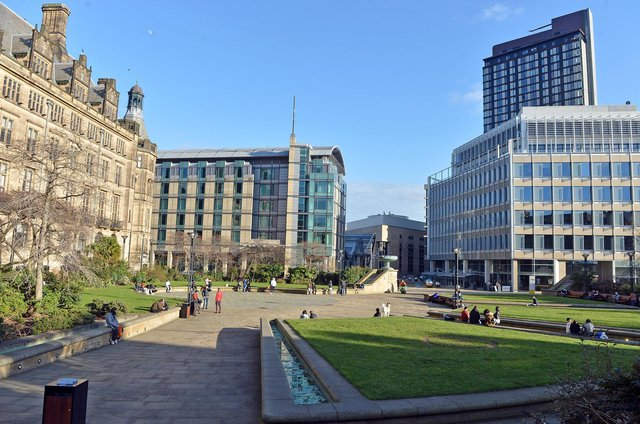 Sheffield City Centre. A few people out enjoying the sun in Sheffield Peace Gardens.
