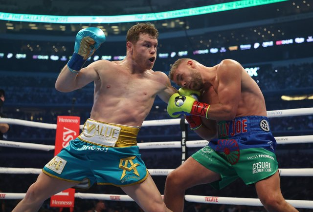 Canelo Alvarez punches Billy Joe Saunders during their fight for Alvarez's WBC and WBA super middleweight titles and Saunders' WBO super middleweight title.