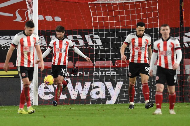 SHEFFIELD, ENGLAND - FEBRUARY 07: Ollie Norwood of Sheffield United looks dejected with team mates after Chelsea's first goal scored by Mason Mount (Not pictured) during the Premier League match between Sheffield United and Chelsea at Bramall Lane on February 07, 2021 in Sheffield, England. Sporting stadiums around the UK remain under strict restrictions due to the Coronavirus Pandemic as Government social distancing laws prohibit fans inside venues resulting in games being played behind closed doors. (Photo by Oli Scarff - Pool/Getty Images)