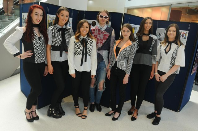 College students take part in a fashion show, displaying upcycled clothing.
