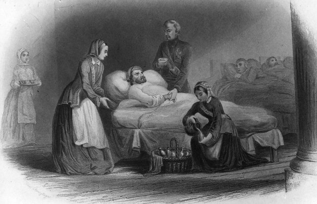 British nurse and hospital reformer Florence Nightingale, standing left, nursing wounded soldiers during the Crimean War